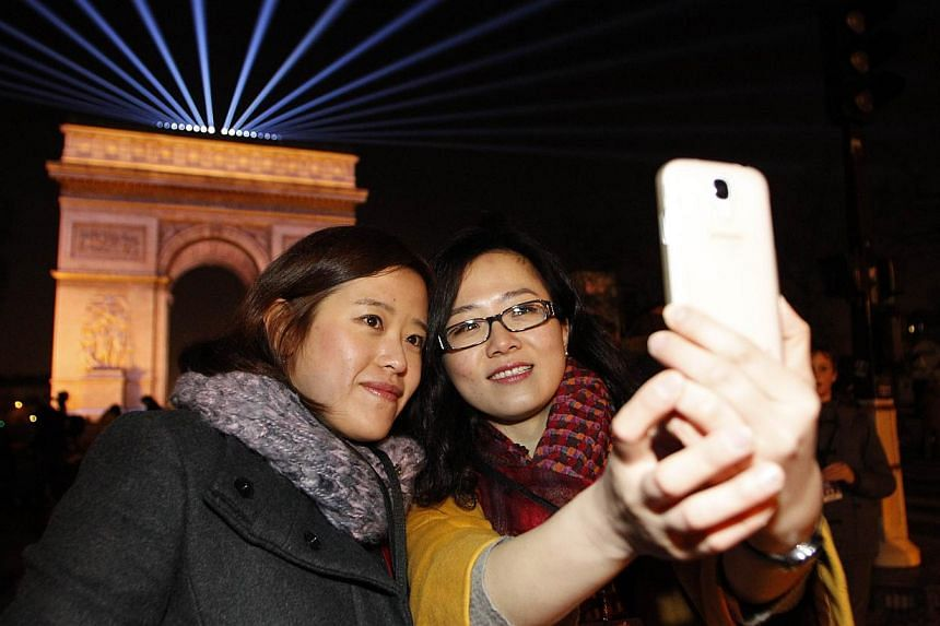 Tourists tom China taking a selfie in front of the Arc de Triomphe on Champs-Elysees avenue in Paris just before midnight on Dec 31, 2014. -- PHOTO: AFP