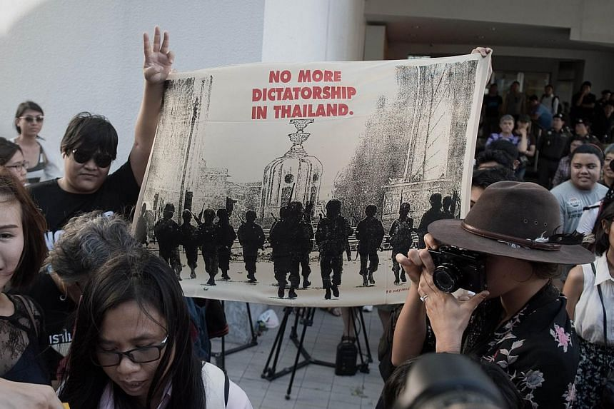 """A demonstrator flashes a """"freedom sign"""" and holds a banner during a rally outside the Art and Cultural centre in Bangkok on Feb 14, 2015. -- PHOTO: AFP"""