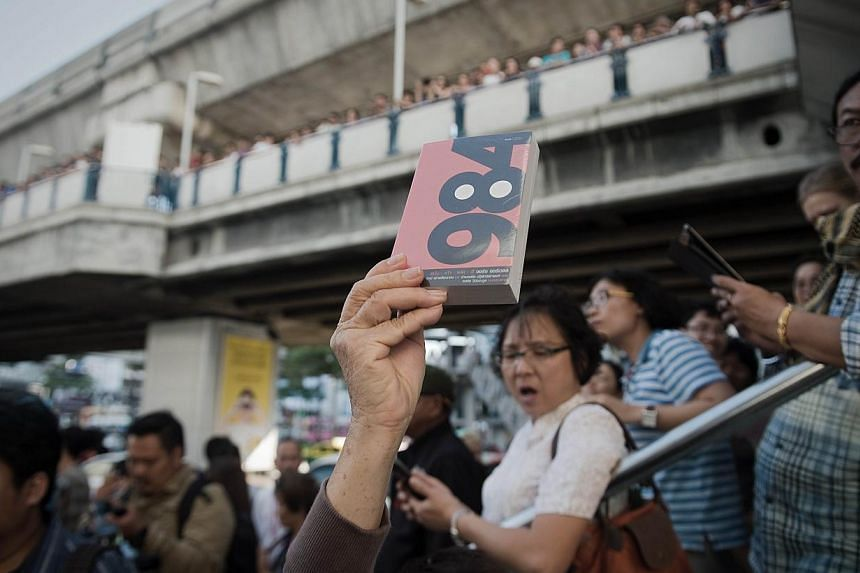 A demonstrator holds up George Orwell's book '1984' during a rally outside the Art and Cultural centre in Bangkok on Feb 14, 2015. -- PHOTO: AFP