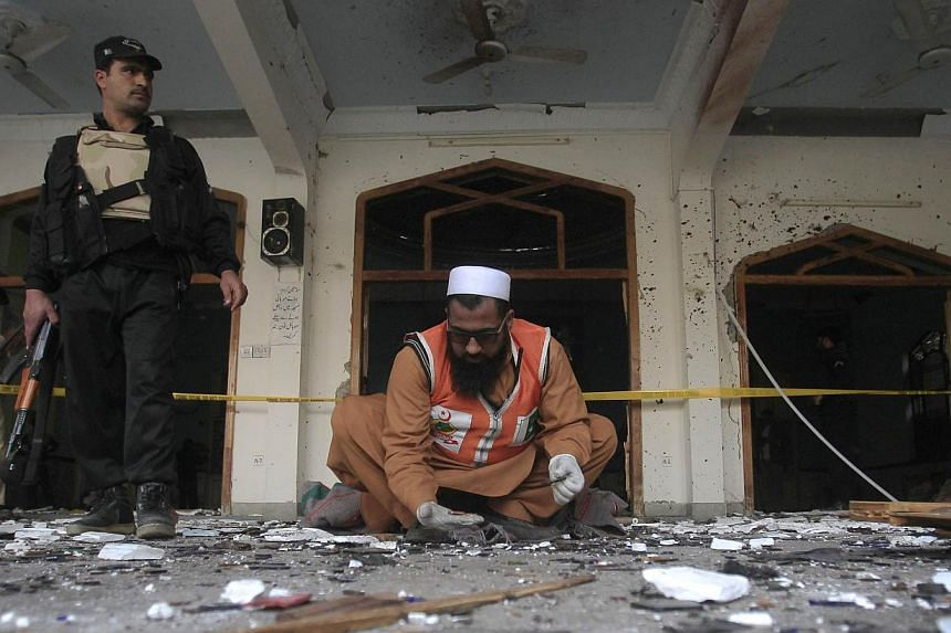 A rescue worker collecting evidence from the site of the explosion in a Shi'ite mosque in Peshawar onFeb 13, 2015. The death toll of the militant attack rose to 21 after an injured person died of his wounds, officials said on Saturday, Feb 14,