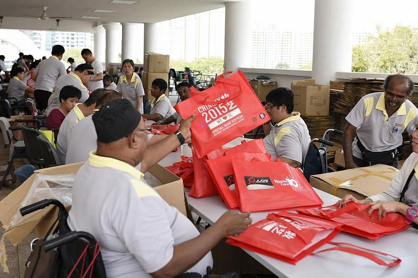Beneficiaries of the SPD, an organisation which represents Singapore's disabled,packing goodie bags for this year's upcoming Chingay Parade. -- PHOTO: SPD