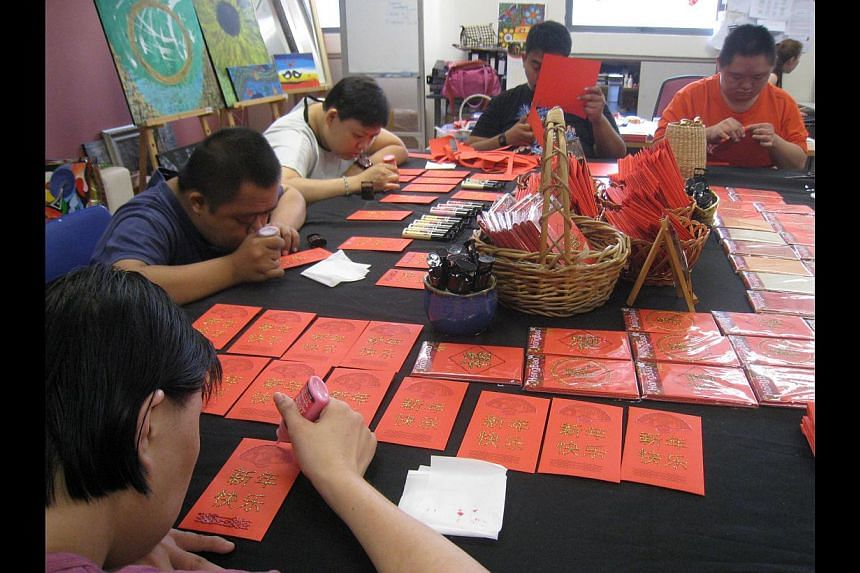 Mr Ang Kian Peng, The SoupRestaurant's businessdevelopment head, on the 100sets of hongbao it boughtfrom Minds last month, whichare hand-made by itsbeneficiaries (above).-- PHOTO: BENSON ANG