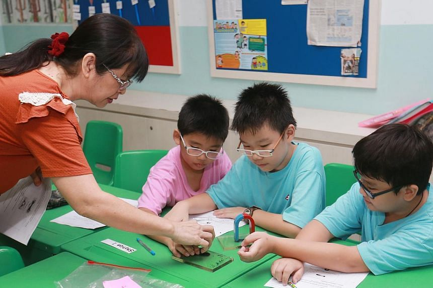 A volunteer helping pupils at a Chinese Development Assistance Council (CDAC) tuition centre in Sengkang. Around 17,600 households benefited from schemes under CDAC last year. -- PHOTO: LIANHE ZAOBAO