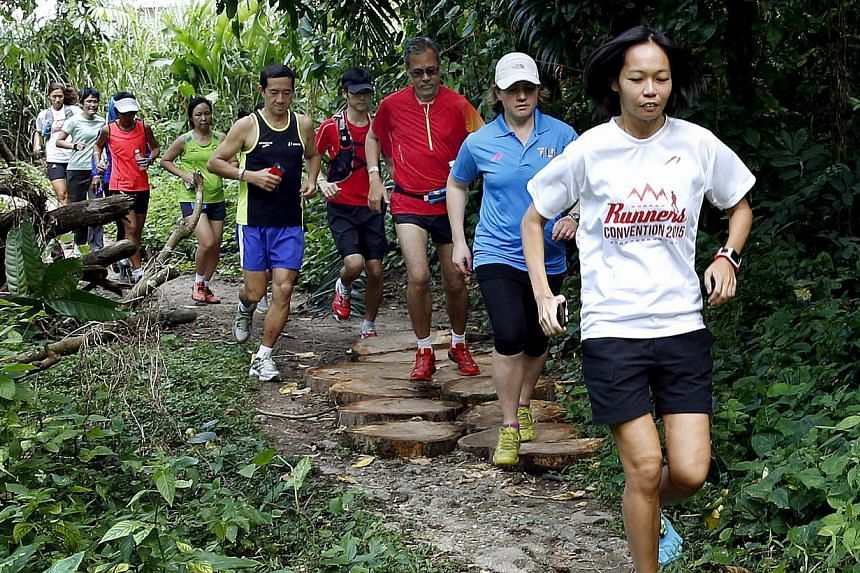 Liew Wei Yong (front) and Lizzy Hawker (second row in blue) running down a trail at Rifle Range Road with the participants. -- ST PHOTO: LAU FOOK KONG