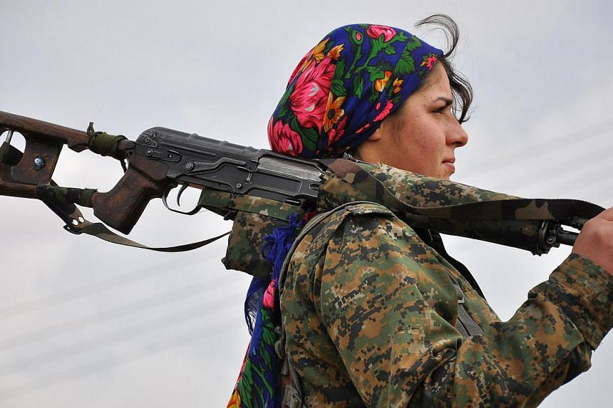 A Kurdish female fighter of the People's Protection Units (YPG) looks on at a training camp in al-Qahtaniyah, known to Kurds as al-Darbassiyah, near the Syrian-Turkish border on Feb 13, 2015. -- PHOTO: AFP