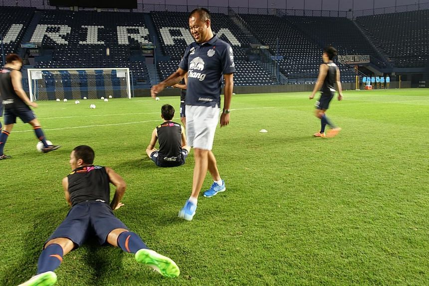 Mr Newin Chidchob (wearing blue shoes) hamming it up with footballers of Buriram United during training. -- ST PHOTO: TAN HUI YEE