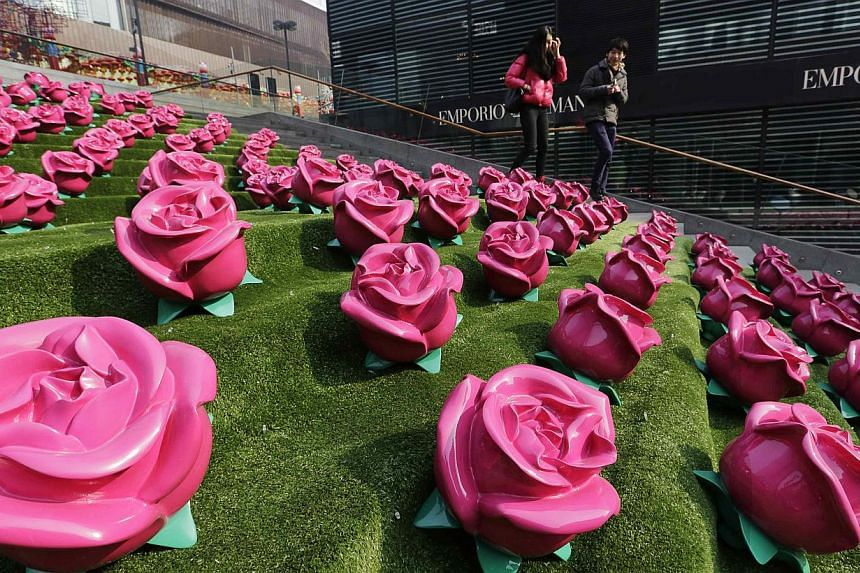 A couple walk past an installation art work of roses at a shopping centre on Valentine's Day, in Beijing on Feb 14, 2015. -- PHOTO: REUTERS