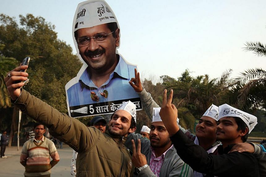 Young Aam Aadmi Party (AAP) supporters taking a selfie with AAP convener Arvind Kejriwal's cutout picture as they celebrate a landslide win in the Delhi Legislative Assembly elections, in Amritsar, India, on Feb 10, 2015. -- PHOTO: EPA
