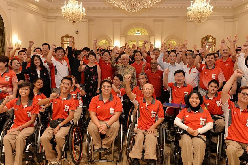 President Tony Tan Keng Yam (centre, standing) flanked by Minister Lawrence Wong on his right, and Minister Tan Chuan-Jin on his left, posing for a group photo with Team Singapore athletes and officials at a reception held at the Istana on Feb 14, 20