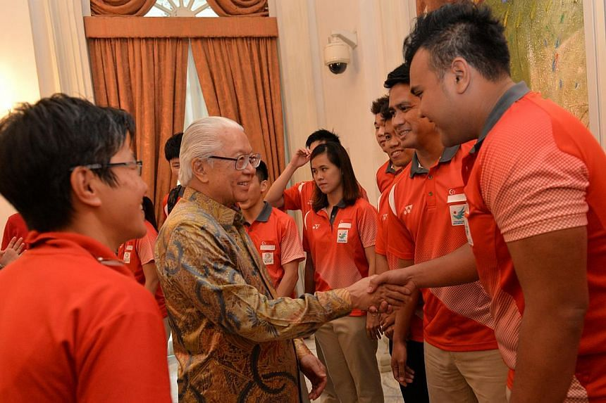President Tony Tan Keng Yam meeting sepak takraw team members Muhammad Danial Feriza Padzil (right) and team captain Mohamad Farhan Amran (second from right), at Istana reception in honour of Team Singapore athletes and their feats at the various maj