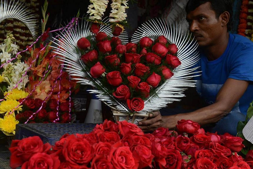An Indian flower seller arranges varieties of roses at a roadside stall ahead of Valentine's Day in Siliguri on Feb 13, 2015. Right-wing Hindus in India are offering white roses, free counselling and a chance to get married for couples caught ki