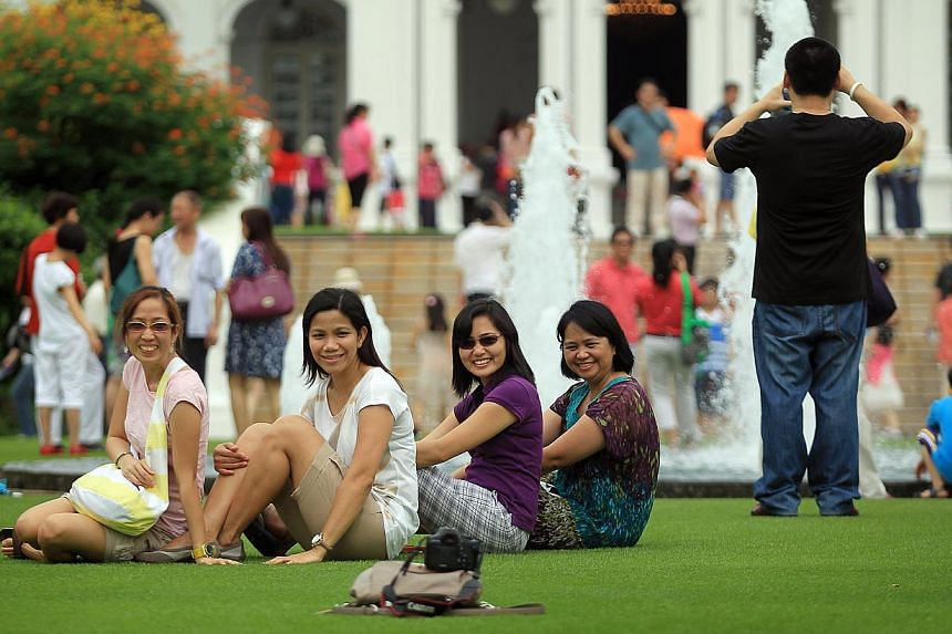 A group of friends on the lawn in front of the Istana building during the open house on Feb 11, 2013. -- ST PHOTO: NEO XIAOBIN