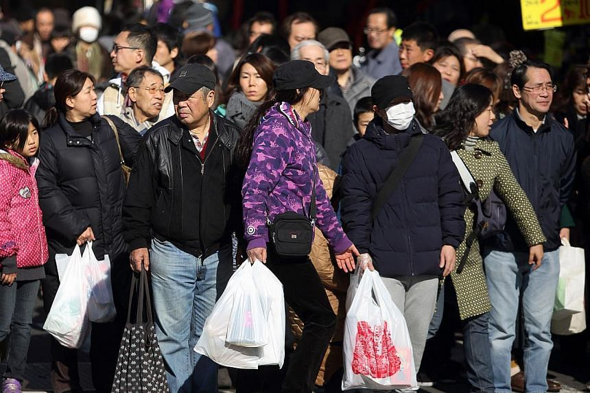 Shoppers waiting to cross a road in the Ameya Yokocho shopping district of Tokyo, Japan, on Dec 30, 2014. Japan's economy rebounded from recession to grow an annualised 2.2 per cent in the final quarter of last year, but the expansion was smaller tha