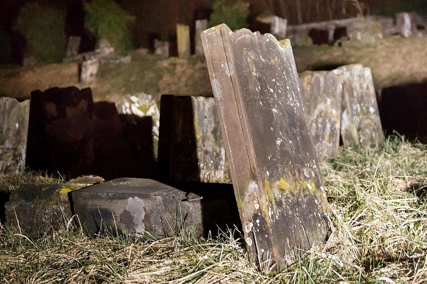 Overturned grave stones in the Jewish cemetery in Saare-Union, France on Feb 15, 2015. Five adolescents aged 15 to 17 have been taken into custody in eastern France for questioning over the vandalism. -- PHOTO: EPA
