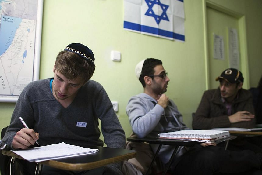 Newly arrived immigrants from France (from left) Jonathan Arbibe and Samuel Chemama and Alexandre Pequito study Hebrew at Ulpan Etzion, in Jerusalem on Jan 20, 2015. French Prime Minister Manuel Valls on Monday, Feb 16, 2015, urged France's Jews