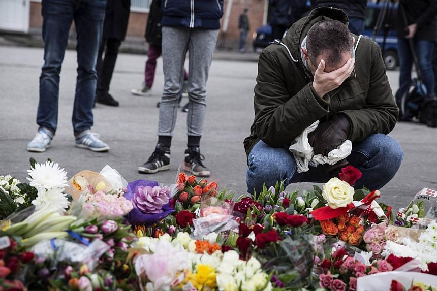 """A man reacts next to flowers for the shooting victims outside the """"Kruttoende"""" cultural centre in Copenhagen, Denmark on Feb 15, 2015.Danish police said on Monday they had charged two people who they detained a day earlier with aiding the man s"""