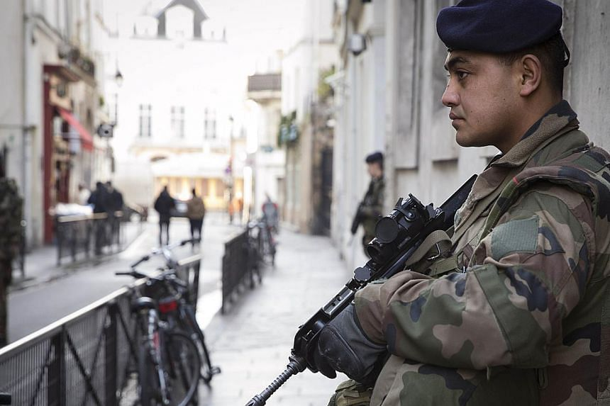 "French soldiers stand guard outside a Jewish school in Paris, on Feb 13, 2015. French Prime Minister Manuel Valls said on Monday, Feb 16, 2015, that the threat of militant attacks in the country remained ""particularly high"" and that exceptional"