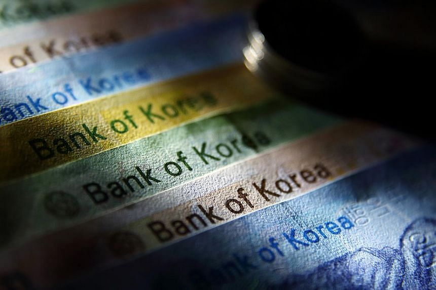 South Korean won banknotes and coins of various denominations are arranged for a photograph in Seoul, South Korea, on Saturday, on Aug 24, 2013. -- PHOTO: BLOOMBERG
