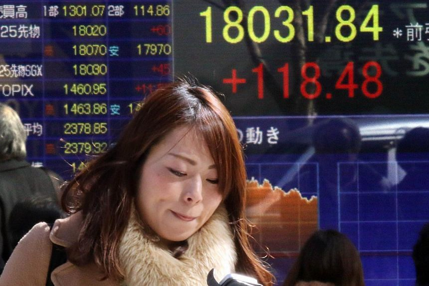 People walking in front of a share prices board in Tokyo on Feb 16, 2015.Tokyo's main stock index closed above 18,000 for the first time in more than seven years on Monday, after official data showed Japan emerged from recession in the last qua