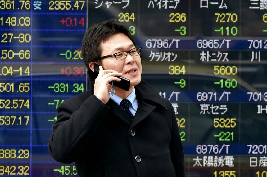 A man talks on a flip-style mobile phone in front of a share prices board in Tokyo on Jan 6, 2015.Japanese shipments of traditional flip-phones rose in 2014 for the first time in seven years while smartphone shipments fell, highlighting Japanes