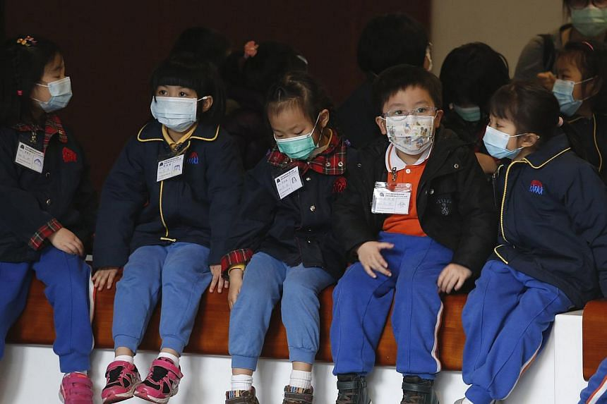 Children in masks visiting Hong Kong's Legislative Council last Friday. The flu death toll so far this year has hit 196, up from 133 early last year.