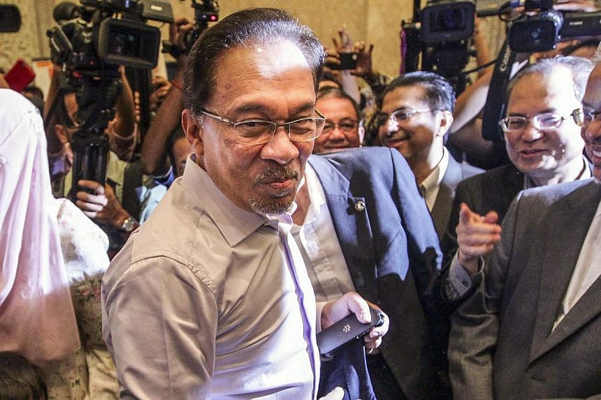 """Malaysian opposition leader Anwar Ibrahim (centre) arriving at the Palace of Justice in Putrajaya, Malaysia on Feb 10, 2015. He is jailed in """"deplorable"""" conditions in a small cell with only a thin foam mattress on the floor, a squat toilet and a buc"""