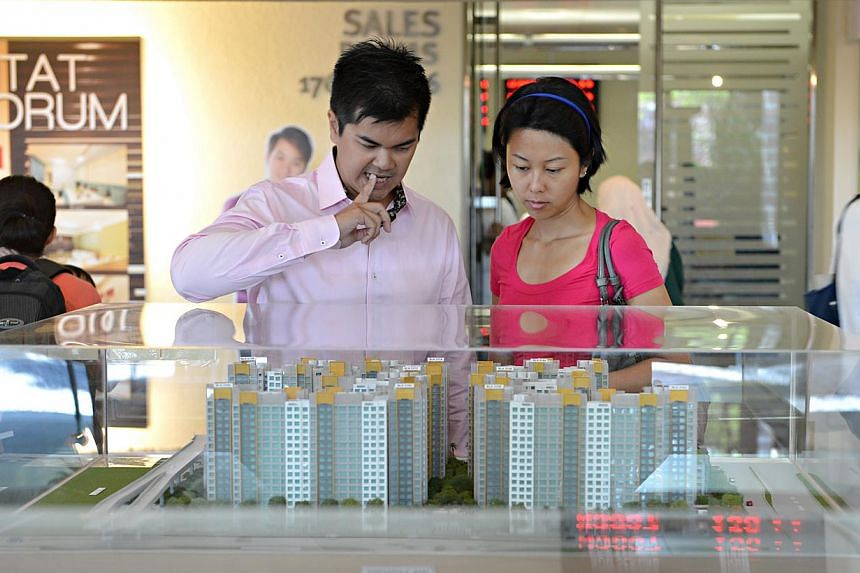 People looking at models of HDB flats. Analysts said a decreased BTO supply last year may have contributed to the dip in the number of applications. There were 22,455 BTO flats offered last year, down from 26,494 in 2013. -- PHOTO: ST FILE