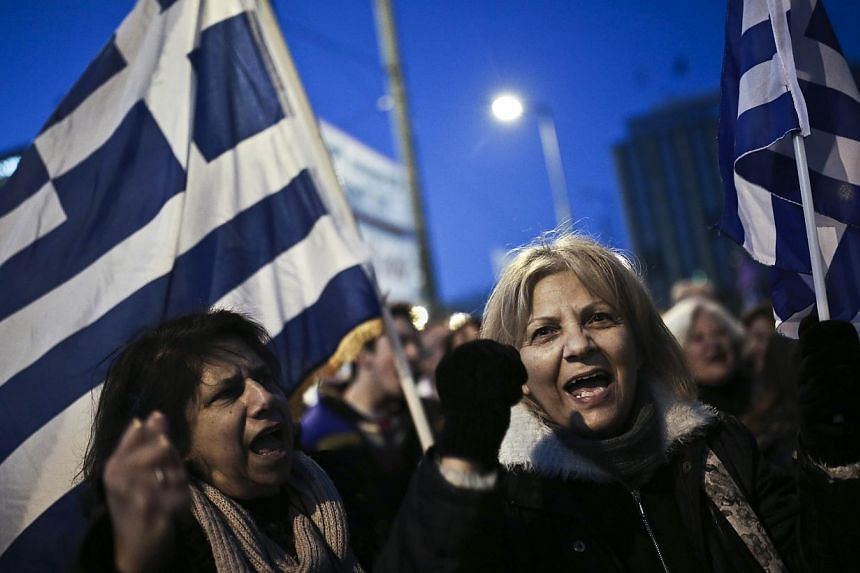 People shout slogans and wave Greek flags during an anti-austerity, pro-government rally in front of the Greek Parliament in Athens on February 15, 2015. -- PHOTO: AFP