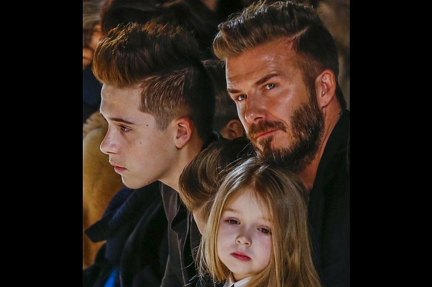 Former England captian David Beckham sits with his son, Brooklyn (left) and his daughter, Harper, during a presentation of the Victoria Beckham Fall/Winter 2015 collection during New York Fashion Week on Sunday. -- PHOTO: REUTERS