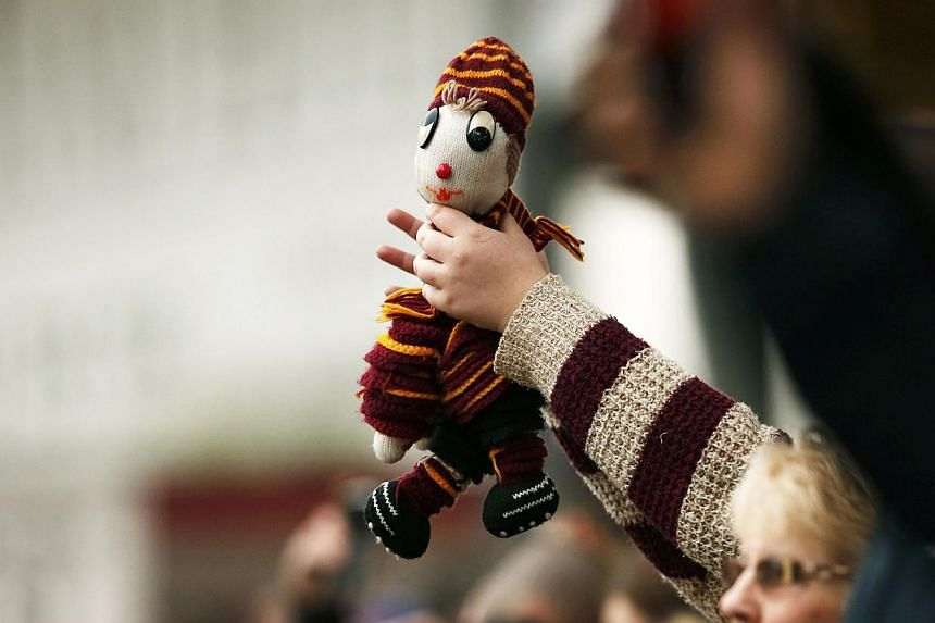 A Bradford City supporter holds a mascot during their FA Cup fifth round soccer match against Sunderland at Valley Parade in Bradford, northern England on Sunday. -- PHOTO: REUTERS