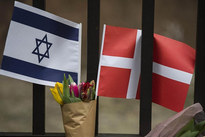A Danish and an Israeli flag are seen among flowers and candles honouring the shooting victims outside the main Synagogue in Copenhagen, Denmark on Sunday, after two fatal attacks in the Danish capital, at a cultural center during a debate on Islam a