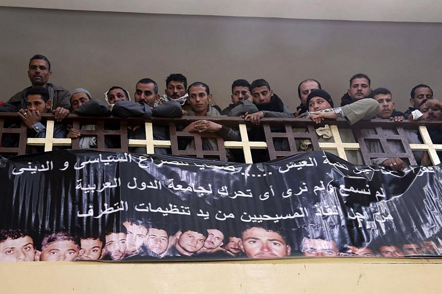 Neighbours and friends of the relatives of Egyptian Coptic men killed in Libya attend mass at a church, as a banner with pictures of the men who were men is displayed on the church wall, in El-Our village, in Minya governorate, south of Cairo Monday.