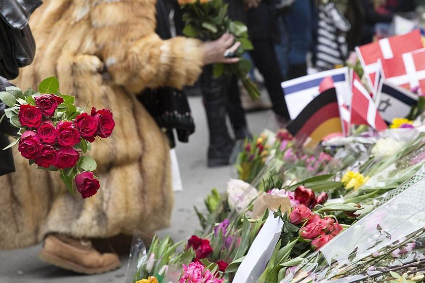 People put flowers to honour the shooting victims outside the main Synagogue of Copenhagen on Monday, after last week-end two fatal attacks.-- PHOTO: AFP