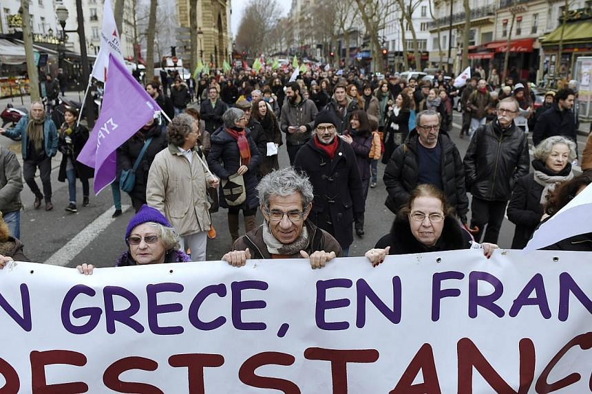"""Protesters hold a banner reading """"In Greece, in France, resistance"""" as they march during a demonstration in support of the Greek people on Sunday in Paris. -- PHOTO: AFP"""