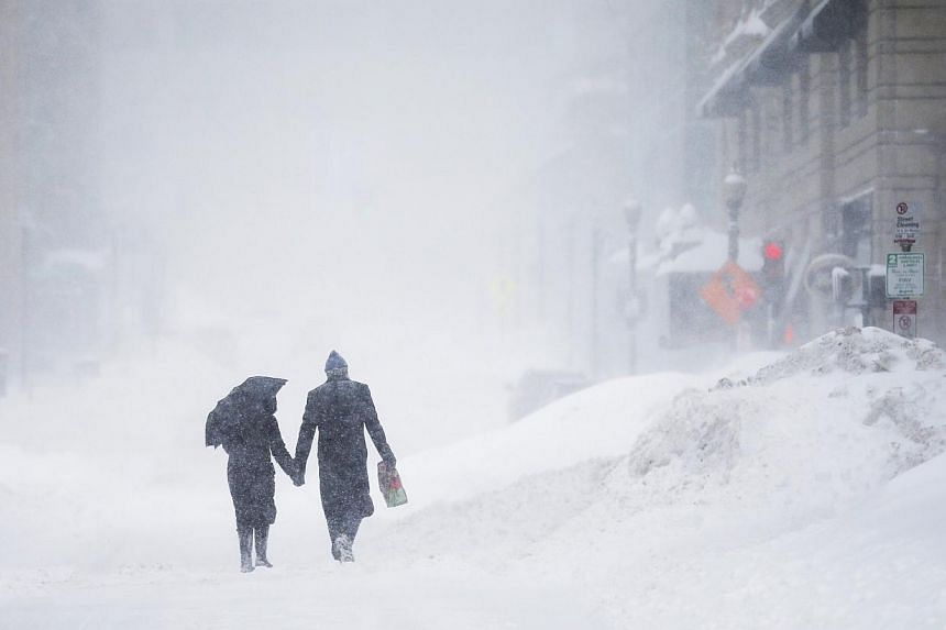 A couple walks hand-in-hand through the snow in the Back Bay during a winter blizzard in Boston, Massachusetts on Sunday. The US Northeast faced yet another major winter storm at the weekend, with blizzard conditions in six states' coastal regions, m