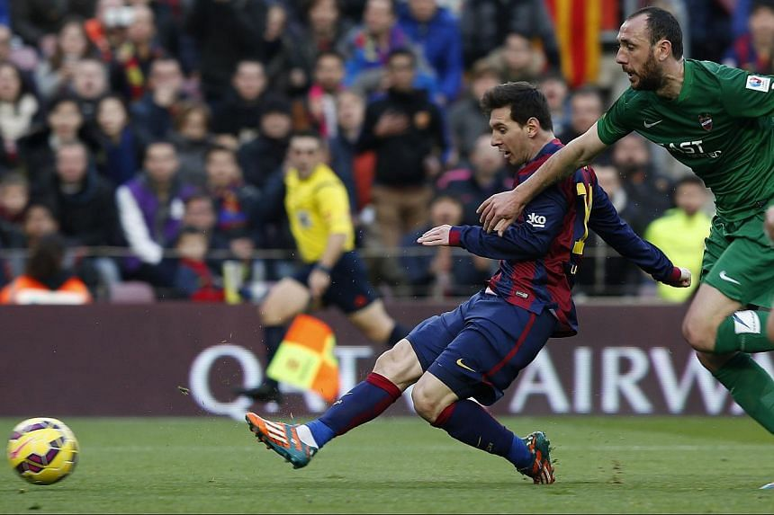 Barcelona's Lionel Messi (L) shoots to score a goal beside Levante's Ivan Ramis during their Spanish first division soccer match at Nou Camp stadium in Barcelona on Sunday. -- PHOTO: REUTERS