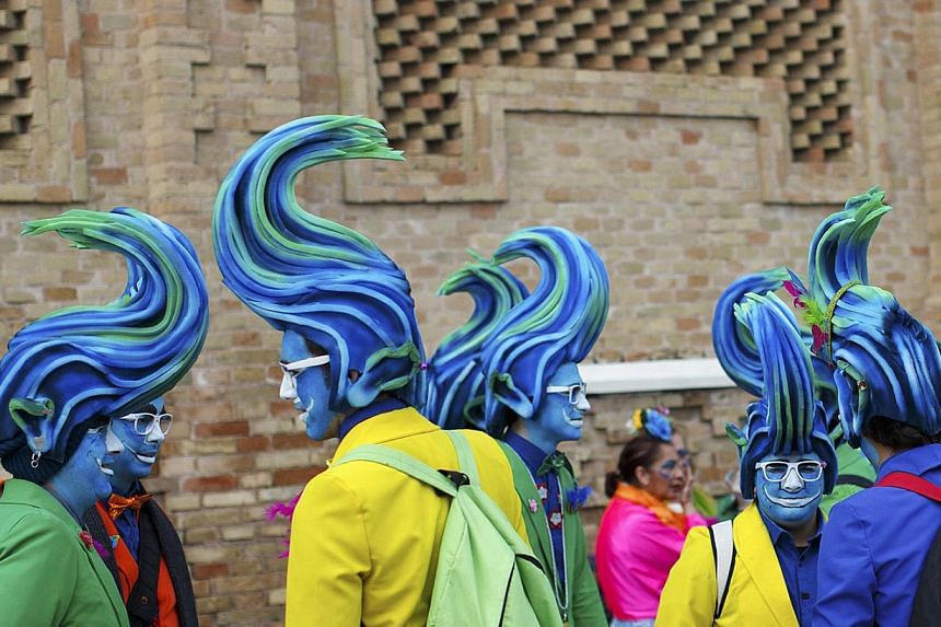 Men in fancy costumes chat during the Carnival of Cadiz, one of the best-known carnivals in Spain, Feb 15, 2015. The whole city participates in the carnival for more than two weeks each year which will run until Feb 22 this year. -- PHOTO: REUTERS
