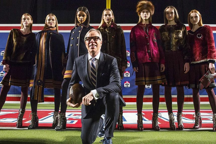 Designer Tommy Hilfiger poses with models before presenting his Fall/Winter 2015 collection at the New York Fashion Week on Feb 16, 2015. -- PHOTO: REUTERS