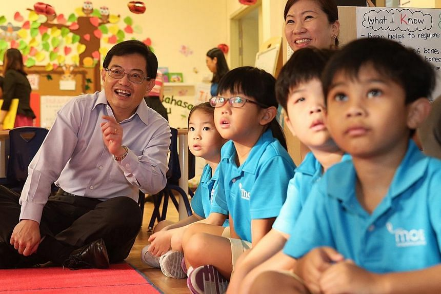 Education Minister Heng Swee Keat watching a Total Defence video with K2 pupils at the MOE Kindergarten at Punggol View Primary School on Tuesday, Feb 17, 2015. -- ST PHOTO: NEO XIAOBIN