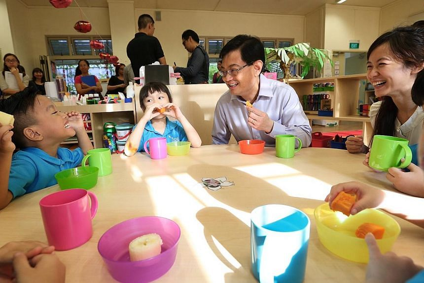 Five-year-old Haziq Aniq (extreme left) showing off his teeth to Education Minister Heng Swee Keat and teacher Elaine Phay, 26, as they eat sweet potatoes and tapioca. -- ST PHOTO: NEO XIAOBIN