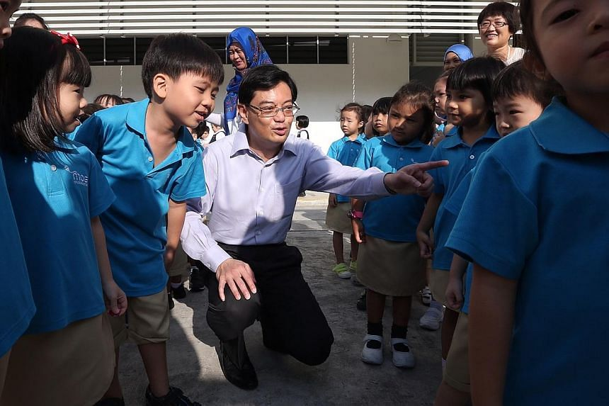Education Minister Heng Swee Keat with kindergarten pupils after a fire drill. -- ST PHOTO: NEO XIAOBIN