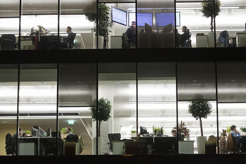 Employees work at their desks in offices inside the headquarters of Kaspersky Lab, a cyber-security firm, in Moscow, Russia, on Dec 9, 2014. -- PHOTO: BLOOMBERG