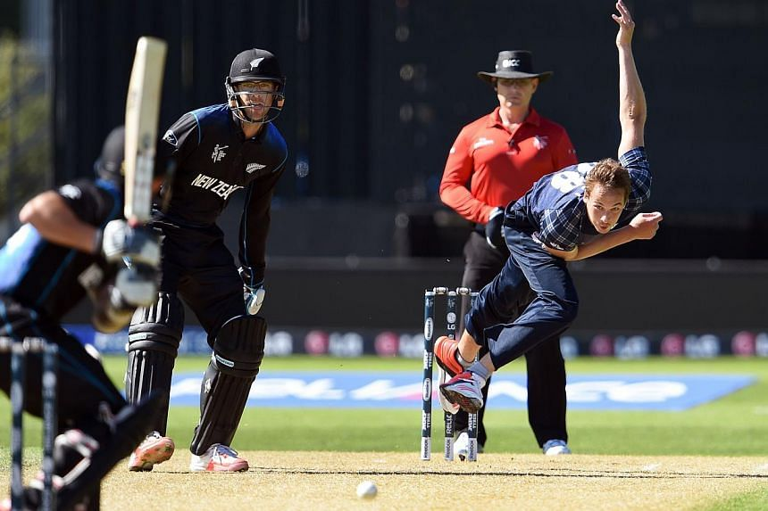 Scotland bowler Josh Davey (right) sends down a delivery to New Zealand batsman Adam Milne (left) as fellow batsman Daniel Vettori (second left) looks on during their 2015 Cricket World Cup match in Dunedin on Feb 17, 2015. New Zealand limped to