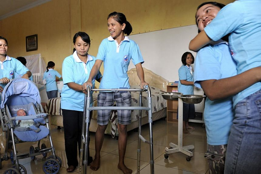 Singapore-bound trainee maids undergoing practical lessons on taking care of the elderly and babies at the PT Dafa Putra Jaya training centre in Semarang, Central Java, in 2011. -- PHOTO: ST FILE