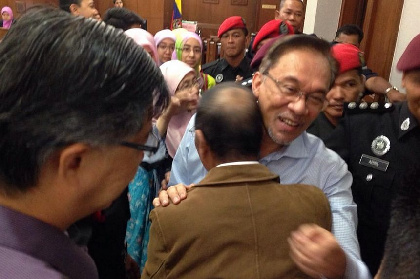 Malaysian opposition leader Anwar Ibrahim hugging his younger brother Rosli at court on Tuesday, Feb 17, 2015. Anwar is in court to give evidence in a defamation suit against Foreign Minister Anifah Aman. -- PHOTO: PARTI KEADILAN RAKYAT (PKR)
