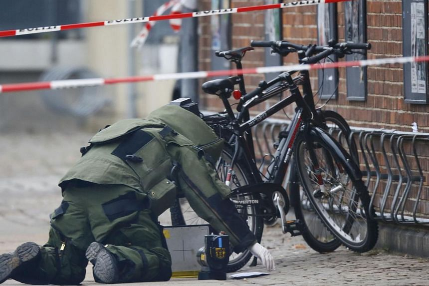 A bomb disposal expert investigates an unattended package in front of a cafe in Oesterbro, Copenhagen on Feb 17, 2015. No explosives were found in the package, Danish police said later on in a twitter message. -- PHOTO: REUTERS