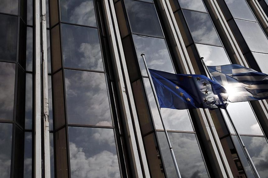 A European Union flag (left) and a Greek national flag flutter as the sky is reflected on a building front in Athens on Feb 17, 2015. -- PHOTO: REUTERS