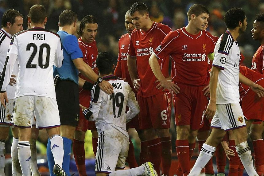 Liverpool's Lazar Markovic (fourth left) looks at FC Basel's Behrang Safari (fifth left) after being sent off during their Champions League Group B soccer match at Anfield in Liverpool, northern England, Dec 9, 2014. -- PHOTO: REUTERS
