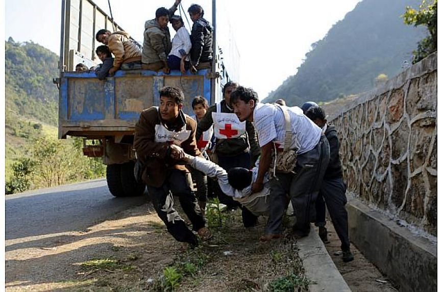 Volunteers of Myanmar Red Cross organisation carry wounded volunteer Moe Kyaw, 45, as the war victims fleeing from Laukkai sit on the truck after vehicles of rescue convoy were attacked by Kokang rebels near self-administered Kokang capital Laukkai,