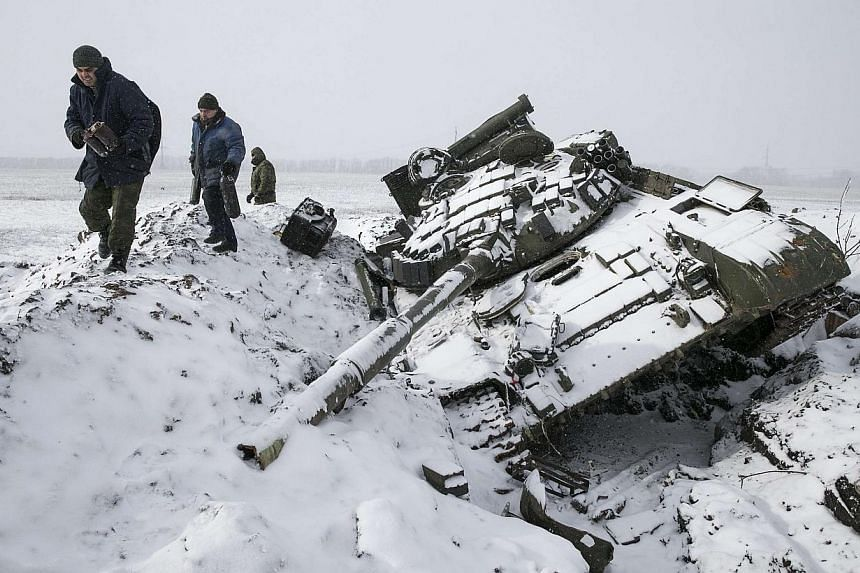 Members of the separatist self-proclaimed Donetsk People's Republic army collect parts of a destroyed Ukrainian army tank in the town of Vuhlehirsk, about 10 km (6 miles) to the west of Debaltseve, on Feb 16, 2015.Ukraine troops and pro-Russian